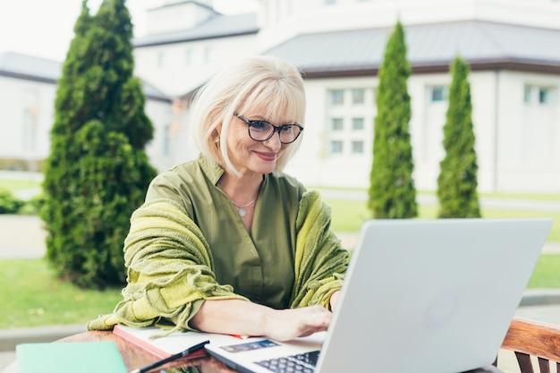 Mulher de negócios sênior bonita sentada em uma cadeira e fazendo anotações em um caderno, com um telefone e um laptop no quintal