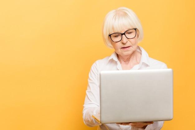 Mulher de negócios sênior com laptop. isolado sobre fundo amarelo.