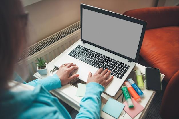 Mulher de negócios sênior com óculos está trabalhando no laptop na mesa, fazendo anotações e digitando