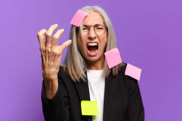 Mulher de negócios sênior com pós adesivo. conceito de negócio humorístico