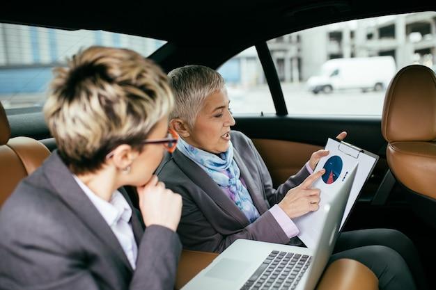 Mulher de negócios sênior e seu assistente sentado na limusine, conversando e trabalhando.