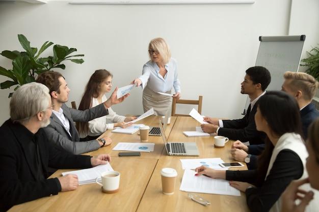 Mulher de negócios sênior, entregando o relatório financeiro ao gerente na reunião de equipe