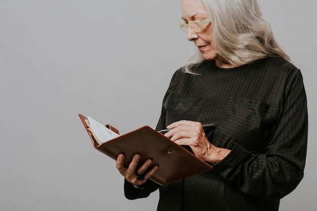 Mulher de negócios sênior escrevendo em um caderno