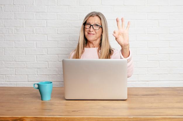 Mulher de negócios sênior que sorri e que olha satisfeita e feliz, contando o número três com dedos.