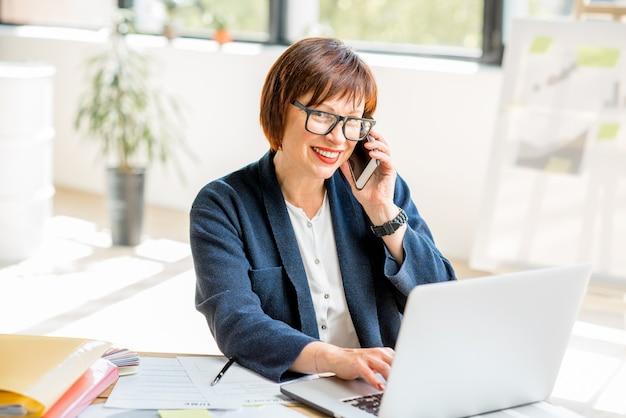 Mulher de negócios sênior trabalhando com laptop e falando ao telefone no interior do escritório moderno e luminoso