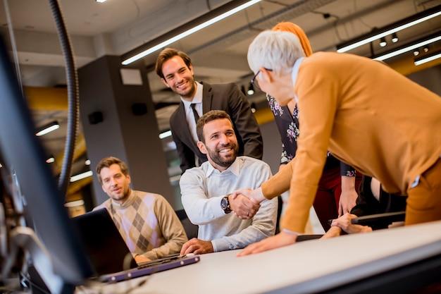 Mulher de negócios sênior trabalhando em conjunto com jovens empresários no escritório moderno