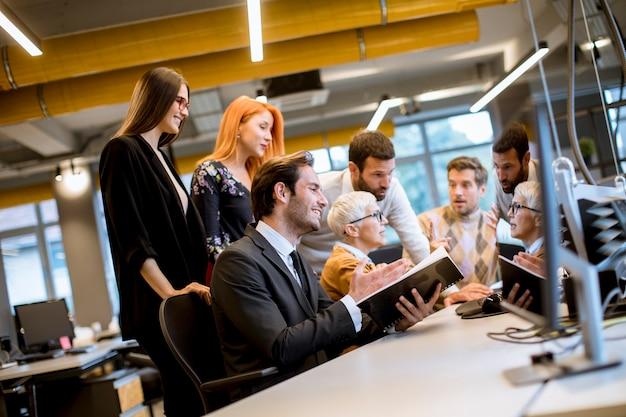 Mulher de negócios sênior trabalhando em conjunto com jovens empresários no escritório