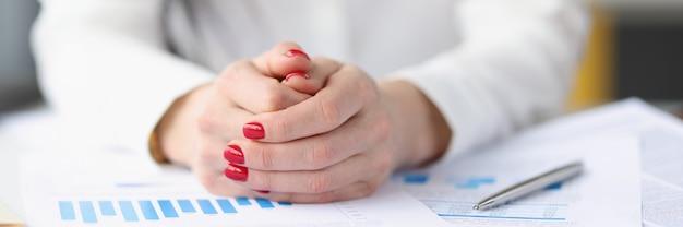 Mulher de negócios sentada à mesa com muitos documentos em papel closeup conceito de emprego