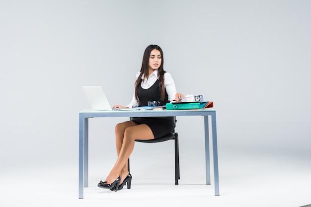 Mulher de negócios sentada à mesa de trabalho com papel isolado em cinza