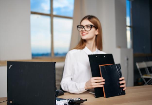 Mulher de negócios sentada à mesa documenta o trabalho do secretário