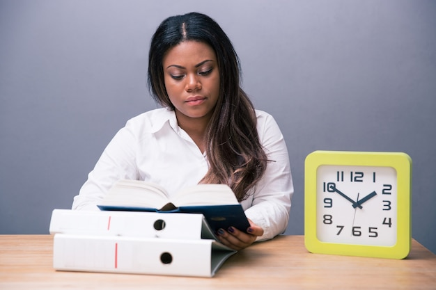 Mulher de negócios sentada à mesa lendo um livro