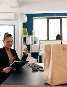 Mulher de negócios sentada à mesa no escritório corporativo lendo estatísticas financeiras na prancheta, antes de saborear a deliciosa comida para viagem em um saco de papel