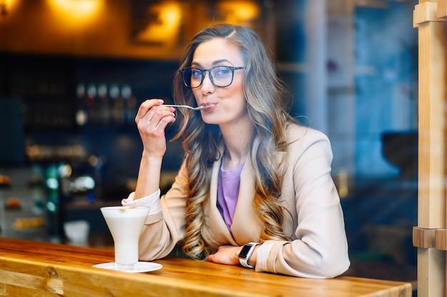 Mulher de negócios, sentada, café atrás da janela, esperando, parceiro de negócios, caucasiano, feminino, descanso, cafeteria, beber, tarde, café, sorrir, olhar, fora