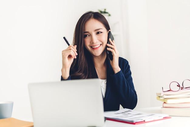 Mulher de negócios sentada e trabalhando com um computador laptop. empresários criativos planejando em sua estação de trabalho no loft de trabalho moderno