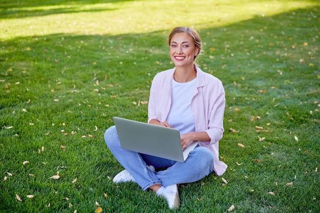 Mulher de negócios sentada na grama do parque de verão usando laptop pessoa de negócios trabalhando remotamente