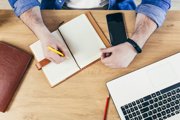 Mulher de negócios sentada na mesa do escritório digitando em um laptop com as mãos fechadas