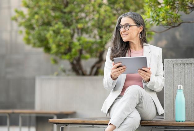 Mulher de negócios sentada na rua com um tablet