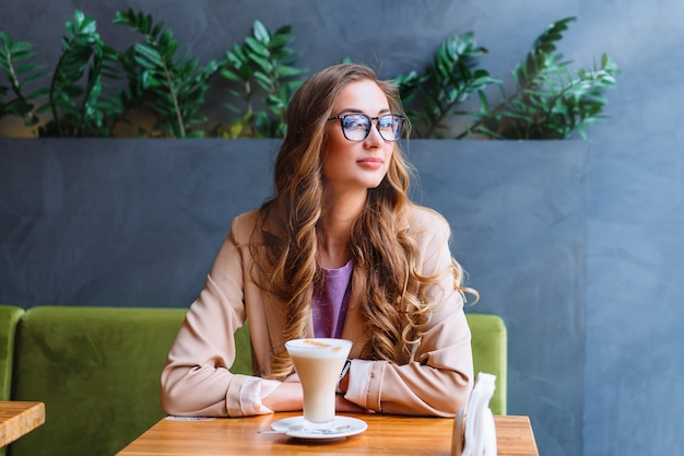 Mulher de negócios, sentada no café perto da janela, esperando parceiro de negócios, caucasiano, feminino, descansando, cafeteria, beber, tarde, café, sorrir, olhando para fora