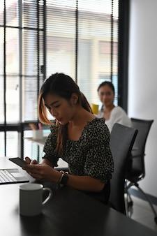 Mulher de negócios sentada no escritório usando telefone celular