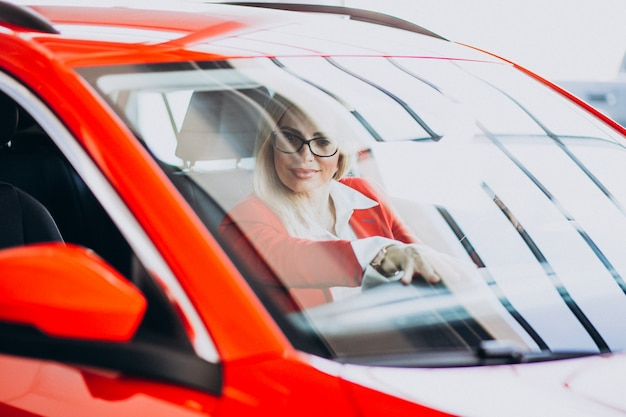 Mulher de negócios, sentado em um carro novo em uma sala de exposições