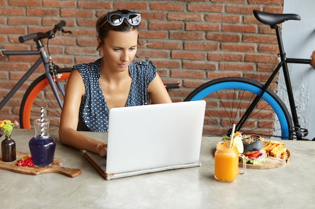 Mulher de negócios séria com máscaras na cabeça, verificando o email em seu computador laptop moderno durante o almoço no fim de semana. mulher independente, usando o notebook para trabalho remoto