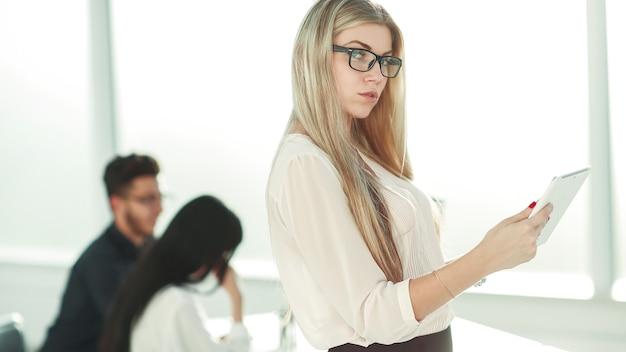 Mulher de negócios séria com tablet digital em pé perto da mesa do escritório