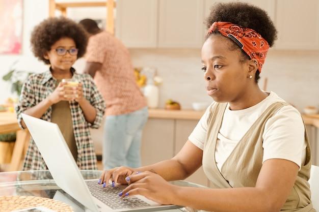Mulher de negócios séria em frente ao laptop na cozinha