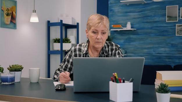 Mulher de negócios séria, madura, de meia-idade, usando laptop, digitando e-mail e escrevendo no caderno, trabalhando em casa, senhora idosa sênior focada em busca de informações na internet ou se comunicando online