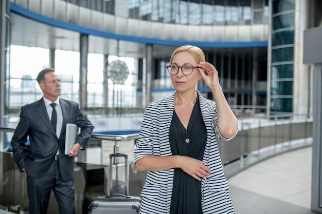 Mulher de negócios sérios com óculos e colega atrás
