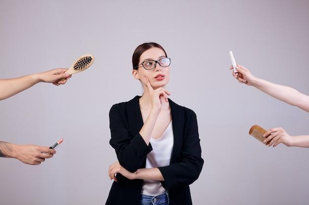 Mulher de negócios sérios está de pé em cinza em uma jaqueta, camiseta branca e óculos de computador. os braços dela se cruzaram. as mãos erradas dão a ela dois pentes e 2 batons. eu não quero trabalhar