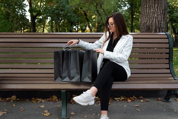 Mulher de negócios sérios está verificando sacolas de compras. descanse no parque após as compras.