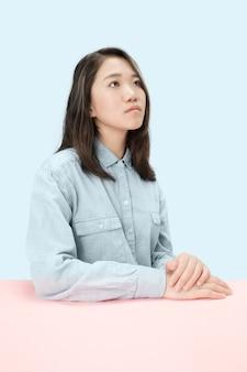 Mulher de negócios sérios sentado à mesa, olhando para cima isolado no fundo azul da moda do estúdio. retrato feminino de meio corpo.