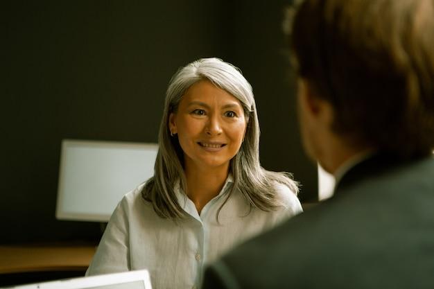 Mulher de negócios simpática e charmosa se comunica com o empresário sentado de costas no primeiro plano