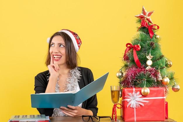 Mulher de negócios sonhadora de terno com chapéu de papai noel e decorações de ano novo, verificando o documento e sentada em uma mesa com uma árvore de natal no escritório