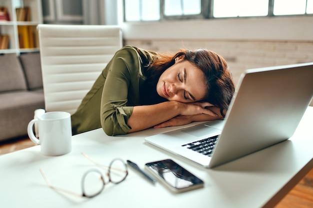 Mulher de negócios sonolenta cansada e estressada adormeceu no laptop enquanto estava sentada à mesa em casa. freelance, trabalhe em casa.