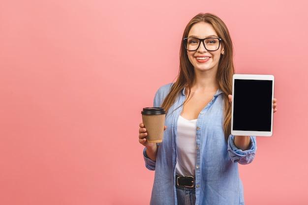 Mulher de negócios sorridente casual mostrando a tela do computador tablet em branco sobre fundo rosa
