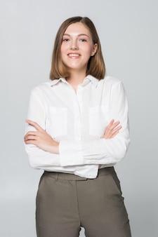 Mulher de negócios sorridente com as mãos postas contra a parede branca. sorriso aberto, braços cruzados.