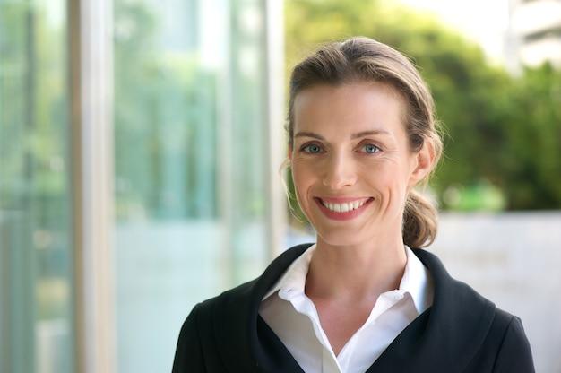Mulher de negócios sorridente com jaqueta preta e camisa branca