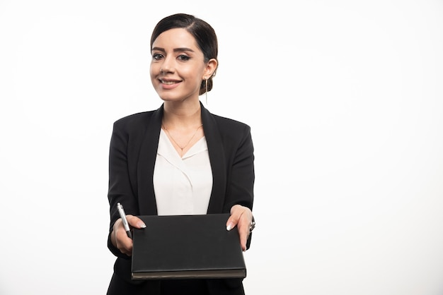Mulher de negócios sorridente com lápis mostrando o caderno.