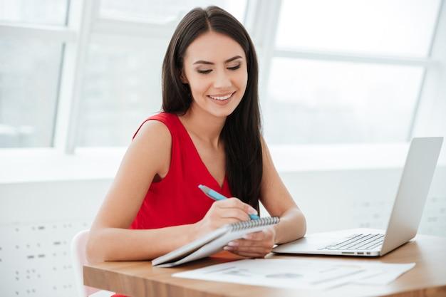 Mulher de negócios sorridente de camisa vermelha sentada à mesa com um laptop e escrevendo algo no escritório