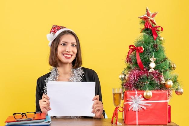 Mulher de negócios sorridente, de terno com chapéu de papai noel e decorações de ano novo, trabalhando sozinha segurando documentos e sentada em uma mesa com uma árvore de natal no escritório