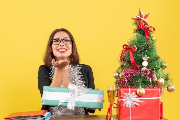 Mulher de negócios sorridente, de terno com óculos, mostrando seu presente, perguntando algo e sentada em uma mesa com uma árvore de natal no escritório