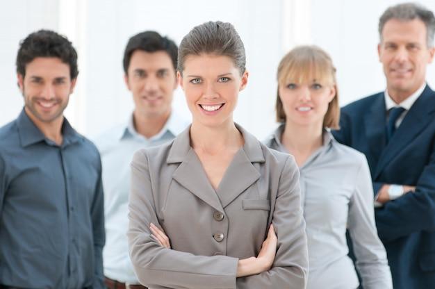 Mulher de negócios sorridente e feliz olhando para a câmera com os colegas no escritório