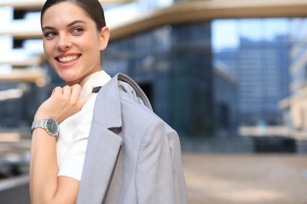 Mulher de negócios sorridente em pé com uma jaqueta por cima do ombro, perto de prédio de escritórios.