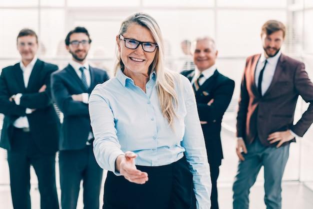 Mulher de negócios sorridente estendendo a mão para um aperto de mão