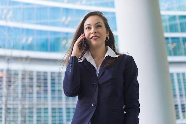 Mulher de negócios sorridente, falando ao telefone