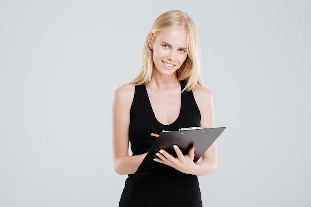 Mulher de negócios sorridente fazendo anotações na prancheta isolada em um fundo branco