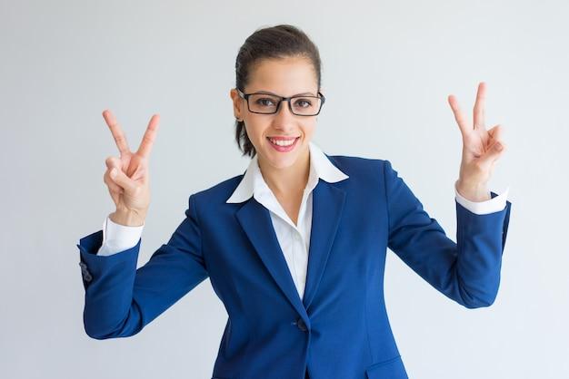 Mulher de negócios sorridente fazendo gesto de vitória com as duas mãos.