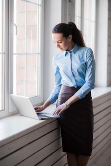 Mulher de negócios sorridente feliz bem sucedida jovem no laptop