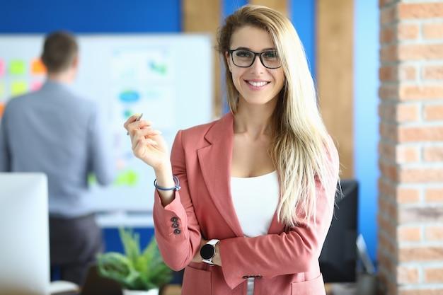 Mulher de negócios sorridente fica no escritório e segura a caneta.